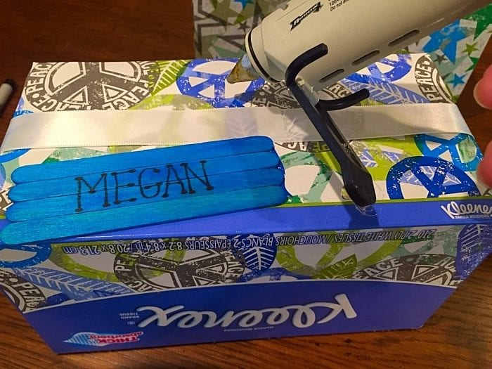 Repurposing a kleenex box into a box to organize school supplies.